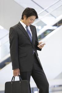 スマートフォンを操作するビジネスマンの写真素材 [FYI02957582]