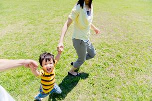 公園を手をつないで走る3人家族の写真素材 [FYI02958180]