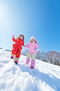 雪の公園で斜面をジャンプする女の子たちの写真素材 [FYI02958185]