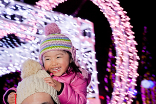 クリスマスイルミネーションの前で父親に肩車される娘の写真素材 [FYI02958188]