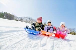 雪の公園でソリ遊びをする子供たちの写真素材 [FYI02958189]