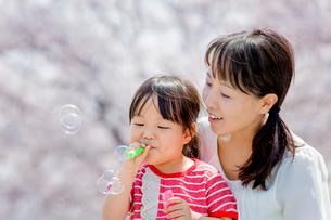 桜の咲く土手でシャボン玉遊びをする母親と娘の写真素材 [FYI02958190]