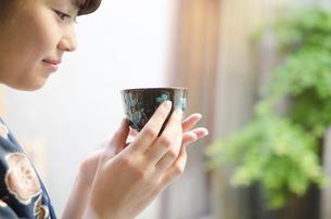 お茶の入った湯のみを持つ着物姿の女性の写真素材 [FYI02958209]
