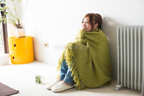 緑の毛布にくるまって座る女性の写真素材 [FYI02958216]