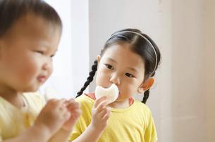 おせんべいを食べている姉妹の写真素材 [FYI02958221]