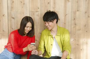 スマホを見ながら笑うカップルの写真素材 [FYI02958224]
