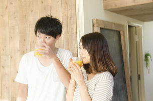 オレンジジュースを飲むカップルの写真素材 [FYI02958225]