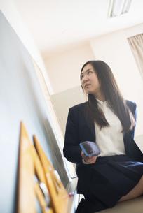 黒板の前で黒板消しを持っている女子高校生の写真素材 [FYI02958227]
