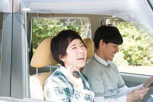 車の鍵を持って笑う女性と笑う男性の写真素材 [FYI02958229]