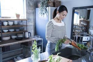 キッチンで野菜を洗っている女性の写真素材 [FYI02958246]