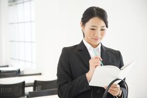 スケジュール帳を見ているスーツ姿の女性の写真素材 [FYI02958256]