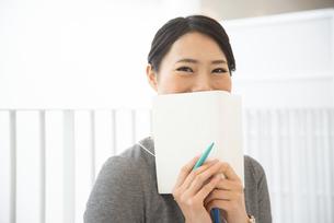 スケジュール帳を持って笑っている女性の写真素材 [FYI02958257]