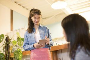 カフェで注文を取っている女性の写真素材 [FYI02958268]
