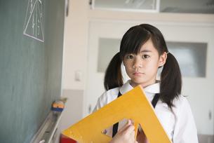 黒板の前に立っている小学生の女の子の写真素材 [FYI02958275]