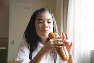 コッペパンを持っている小学生の女の子の写真素材 [FYI02958281]