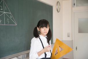 黒板の前で三角定規を持っている小学生の女の子の写真素材 [FYI02958302]
