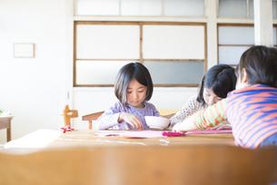 テーブルで遊んでいる姉妹の写真素材 [FYI02958311]