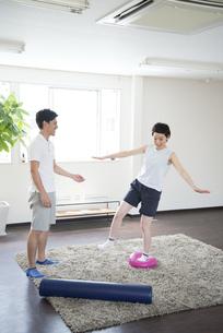 室内でトレーニングをする女性とトレーナーの写真素材 [FYI02958317]
