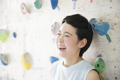 ボルダリングの壁の前で笑う女性の写真素材 [FYI02958328]