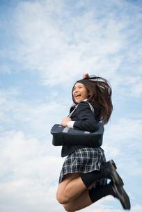 ジャンプをしている制服姿の女子高生の写真素材 [FYI02958346]