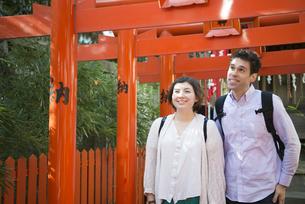 赤い鳥居をくぐる外国人観光客の写真素材 [FYI02958350]