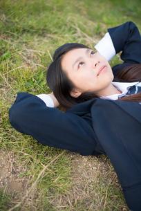 草むらに寝そべっている制服姿の女子高生の写真素材 [FYI02958355]
