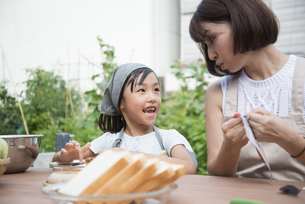 庭で食事の用意をする親子の写真素材 [FYI02958361]