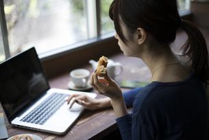 ドーナツを食べながらカフェでパソコンを触っている女性の写真素材 [FYI02958388]