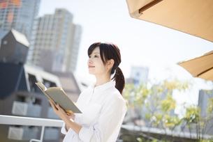 屋上で本を持っている女性の写真素材 [FYI02958389]