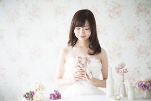 ウェディングドレスを着て花を持っている女性の写真素材 [FYI02958402]