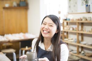陶芸教室で作品を持って笑っている女性の写真素材 [FYI02958405]