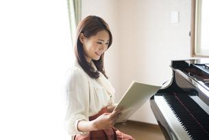 ピアノの前で楽譜を見ている女性の写真素材 [FYI02958412]