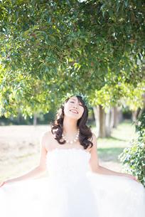 ドレスを広げて笑っているウェディングドレス姿の女性の写真素材 [FYI02958418]
