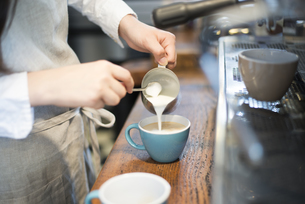エスプレッソにミルクを注いでいる女性の手の写真素材 [FYI02958425]