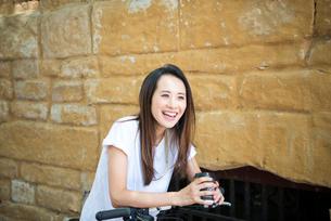 自転車にもたれてコーヒーを飲んでいる女性の写真素材 [FYI02958432]