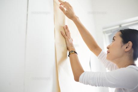 壁に模造紙を貼っている女性の写真素材 [FYI02958435]