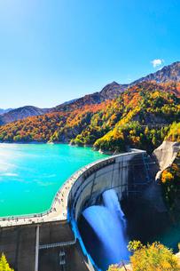 秋の立山 黒部ダム観光放水と紅葉の山並みの写真素材 [FYI02958579]