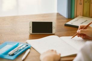 スマートフォンを見ながら勉強する女子学生の写真素材 [FYI02958625]