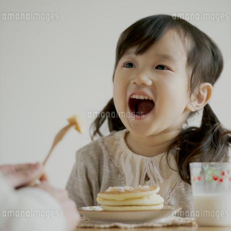 ホットケーキを食べさせてもらう女の子の写真素材 [FYI02958757]