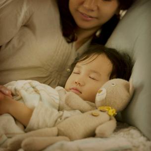 ベッドで眠る女の子と母親の写真素材 [FYI02958760]