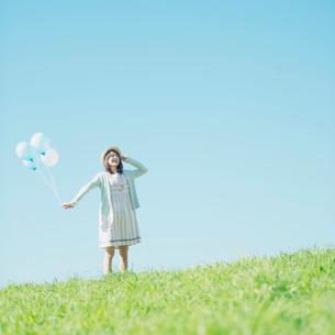 草原で風船を持ち微笑む女性の写真素材 [FYI02958764]