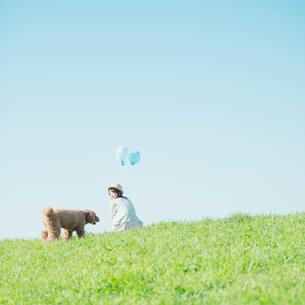 草原で風船を持つ女性と犬の写真素材 [FYI02958766]
