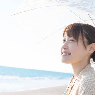 海で日傘をさし微笑む女性の写真素材 [FYI02958772]