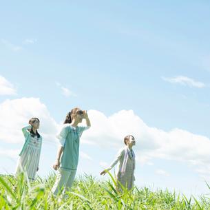 草原で空を見上げる3人の女性の写真素材 [FYI02958793]