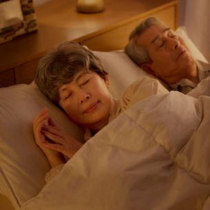 ベッドで眠るシニア夫婦の写真素材 [FYI02958813]