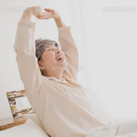 ベッドで伸びをするシニア女性の写真素材 [FYI02958816]