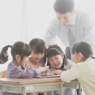 タブレットPCで勉強をする小学生と先生の写真素材 [FYI02959175]