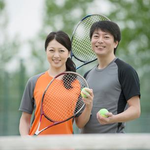 テニスラケットを持ち微笑むミドル夫婦の写真素材 [FYI02959203]