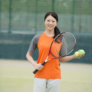 テニスラケットを持ち微笑むミドル女性の写真素材 [FYI02959208]