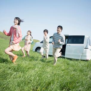車から駆け出す若者たちの写真素材 [FYI02959209]